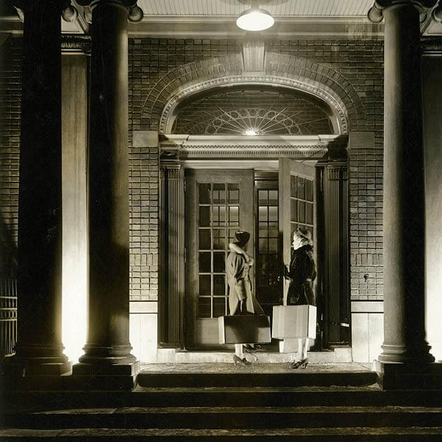1910s photo of two women with suitcases opening heavy door