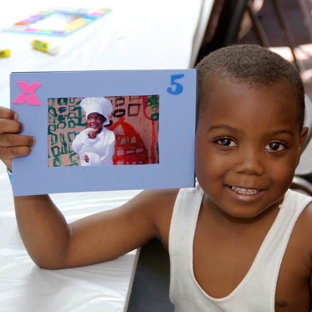 200s photo of child holding a photo of himself dressed up as a chef