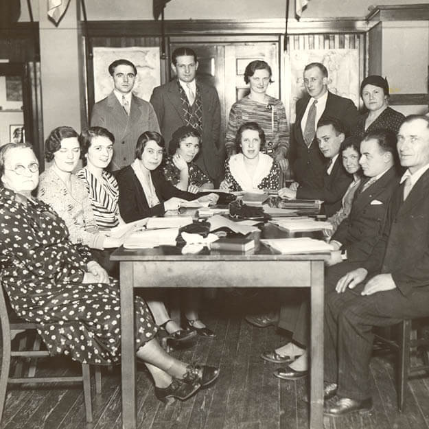 1930s photo of group of people sitting around table