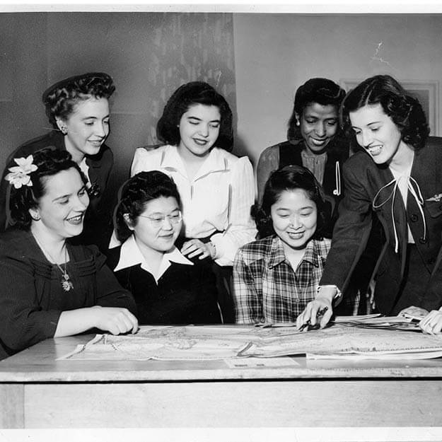 1940s photo of multi ethnic woman huddled around table looking at map