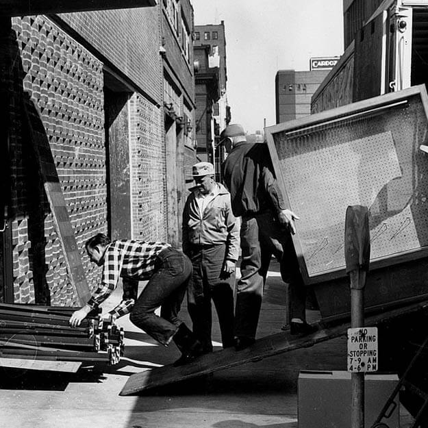 1960s black and white photo of movers moving furniture into a building