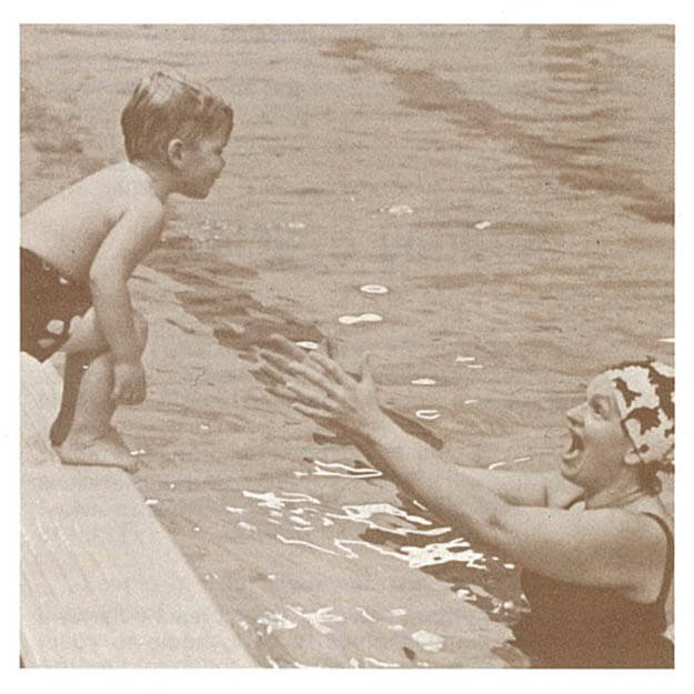 1970s photo of boy child jumping off pool ledge into his mother's arms