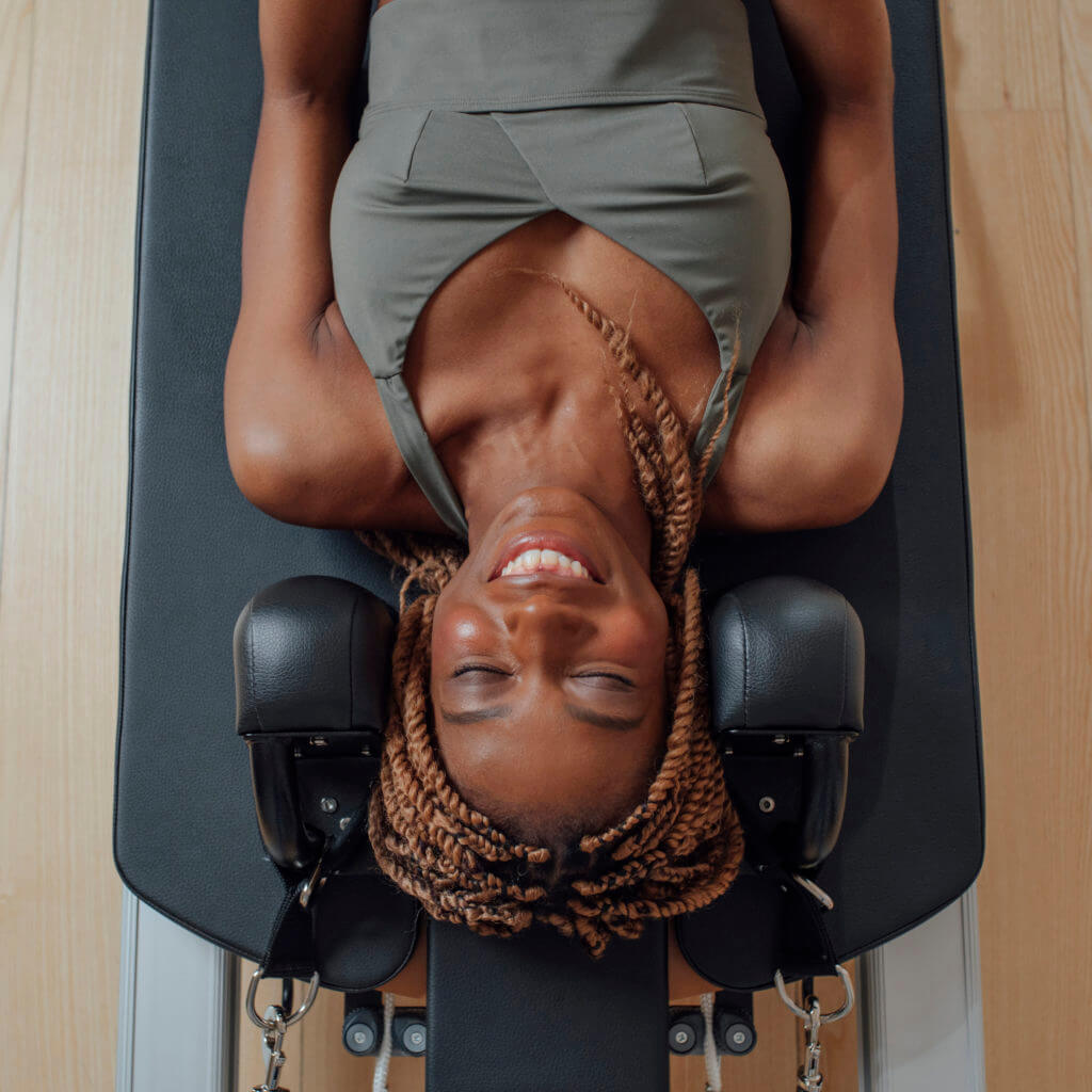 From above photo of pretty African smiling woman in sportswear lying on pilates reformer.