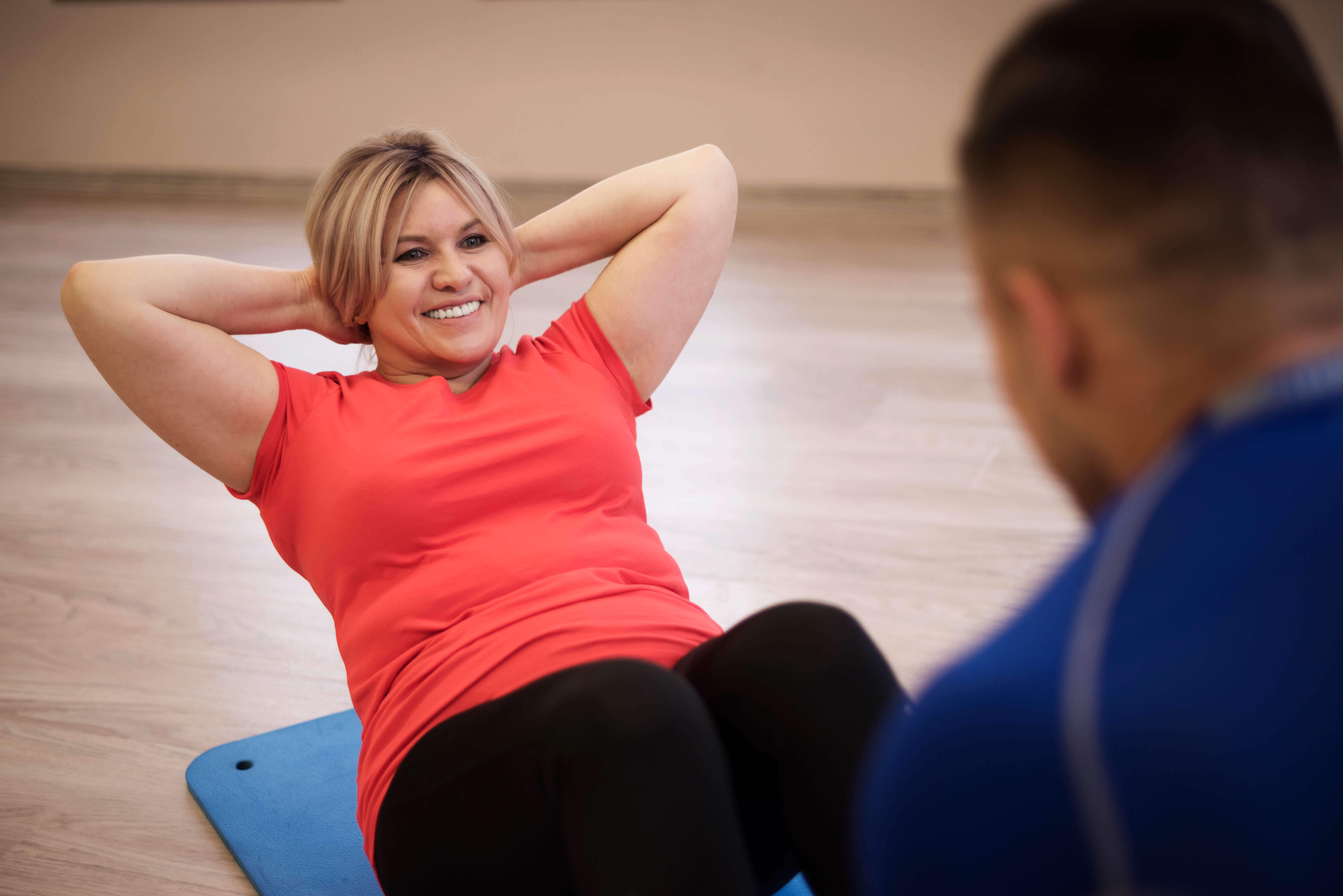 Personal trainer holding the feet of a mature woman doing crunches