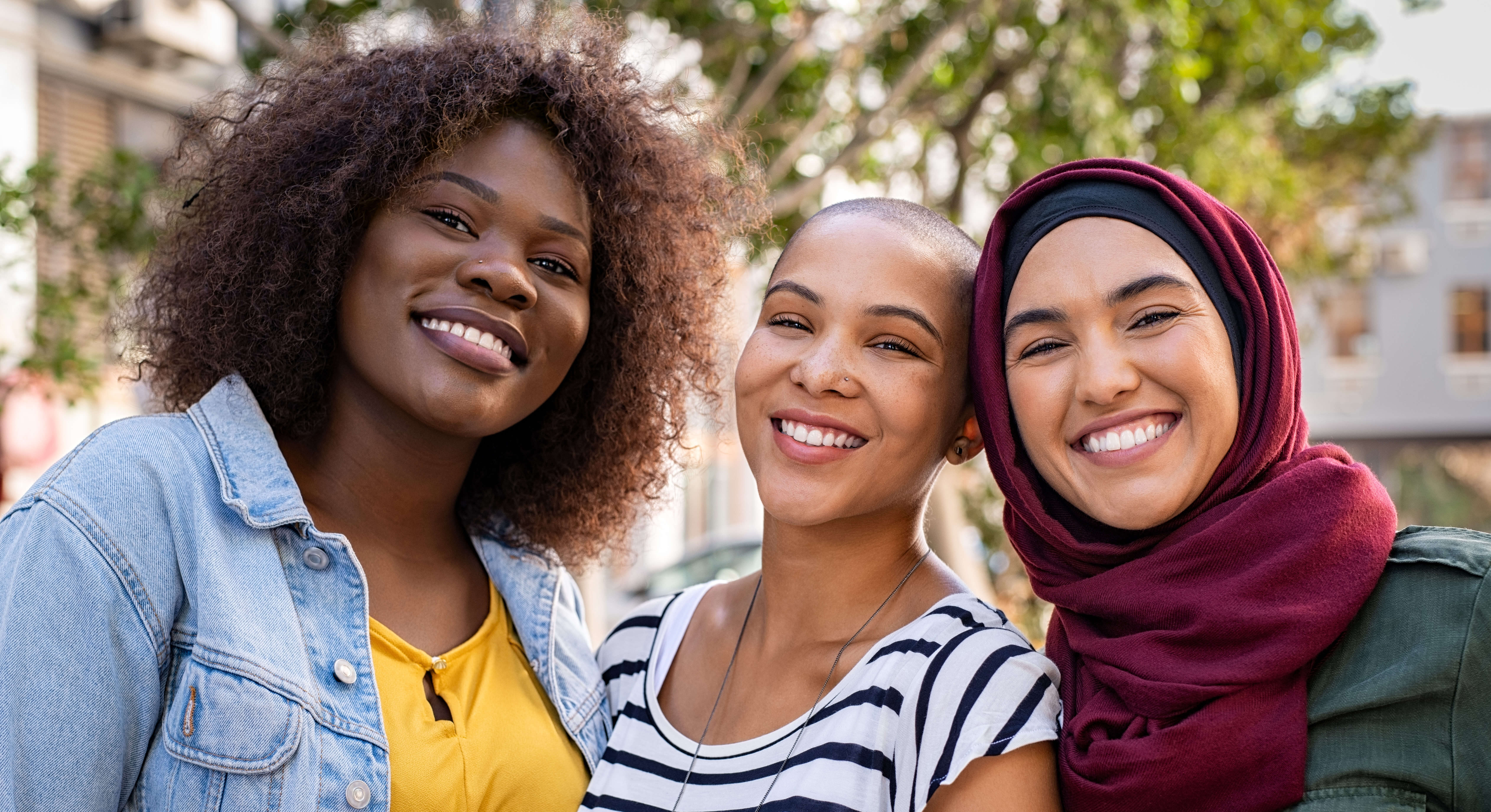 three happy multiethnic young women smiling and looking a the camera