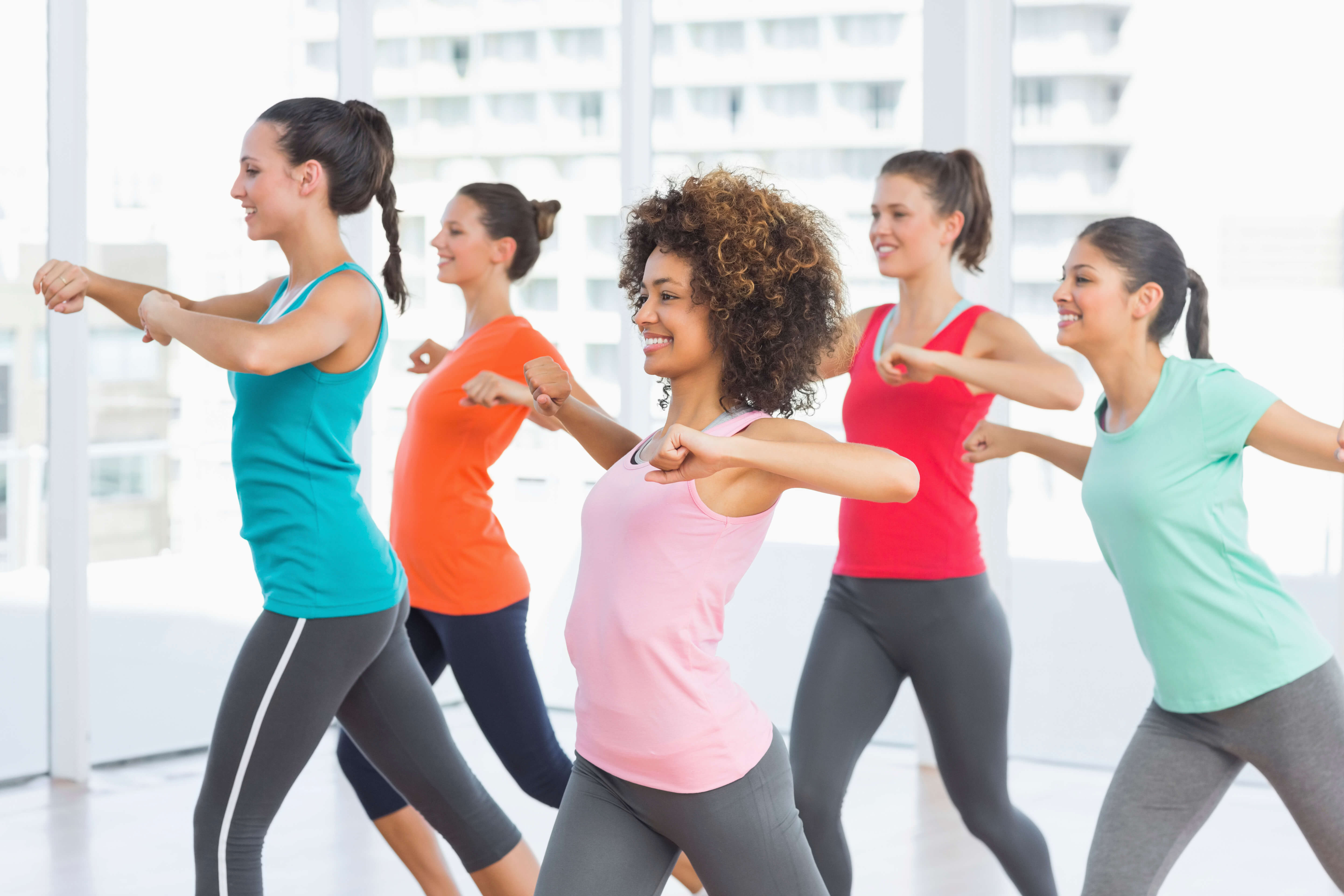 Multicultural group of women doing a dance based exercise class