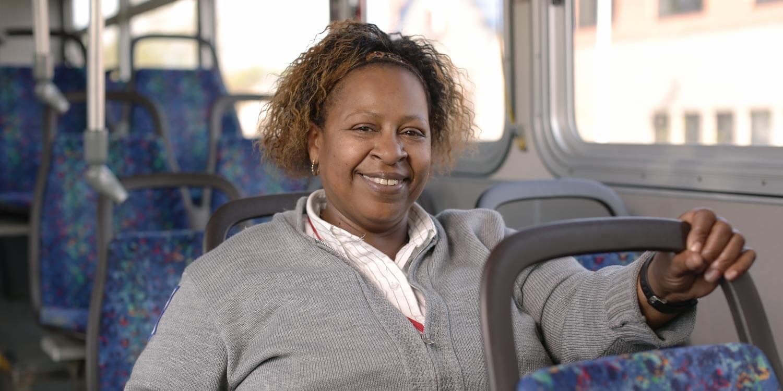 Monique smiling at camera on MetroTransit bus, wearing her work uniform