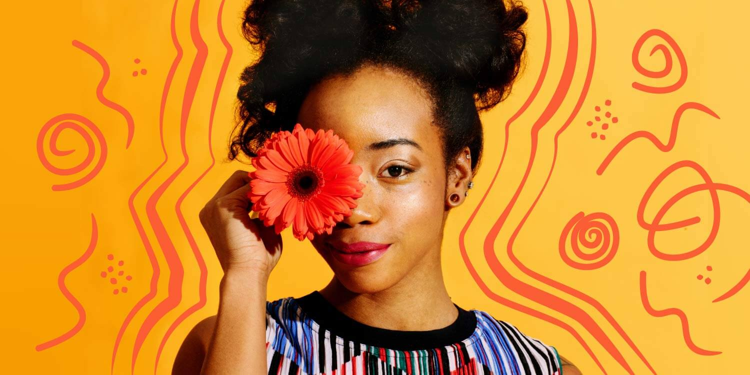 Young African American woman smiling and while holding an orange flower in front of her face. The background is a yellow gradient with orange doodles.