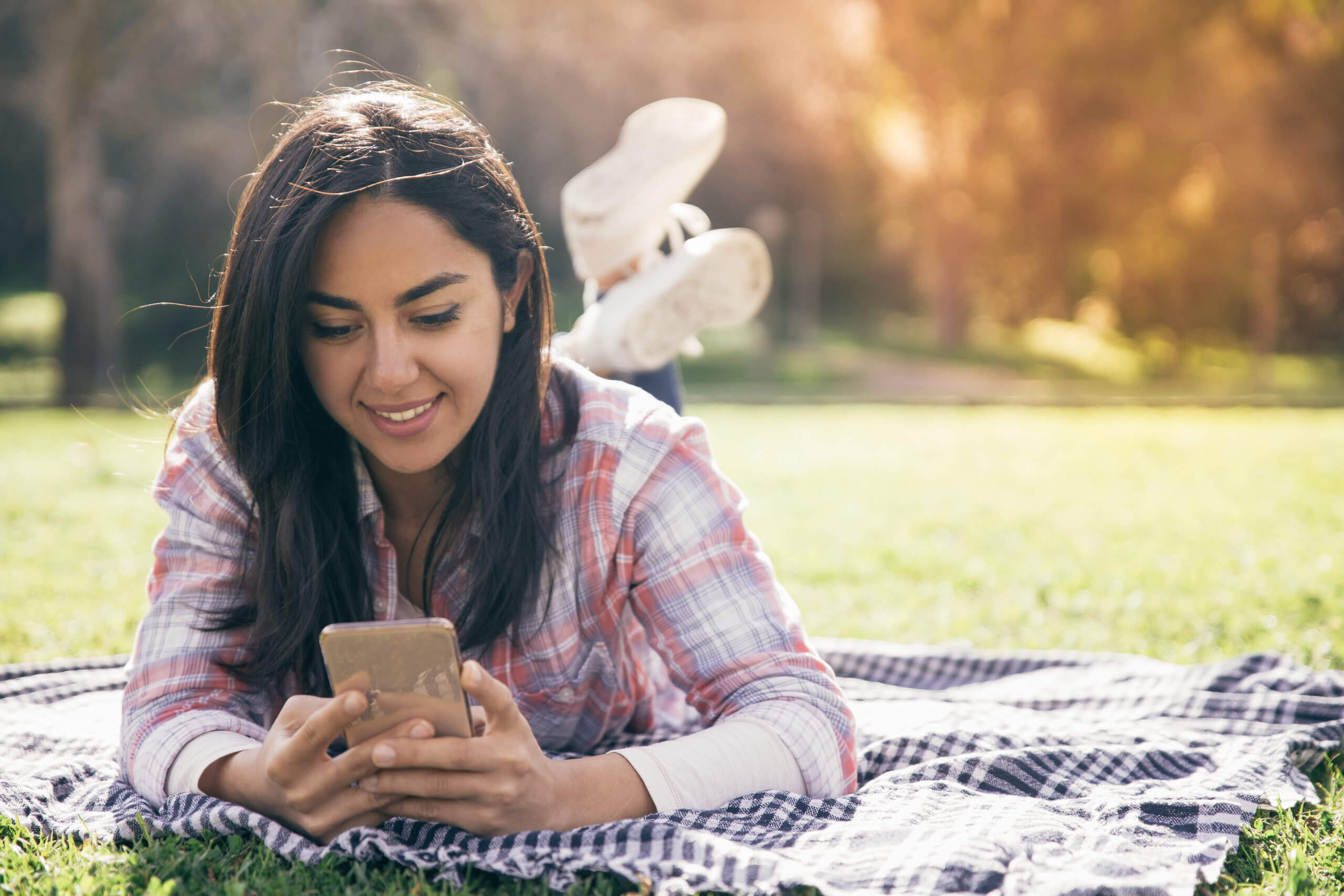 Smiling focused girl typing message on smartphone in park.