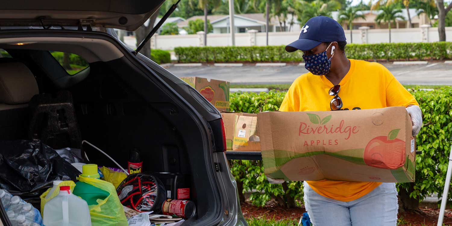 Volunteer wearing face mask loading a box of donated goods into the trunk of a car