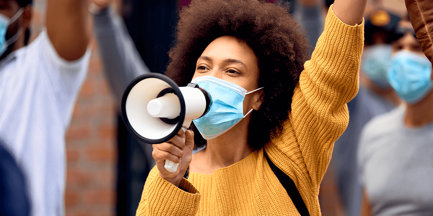 Young African American woman shouting through megaphones at protest