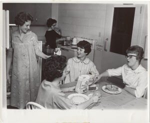black and white photo of young women having bread in the kitchen