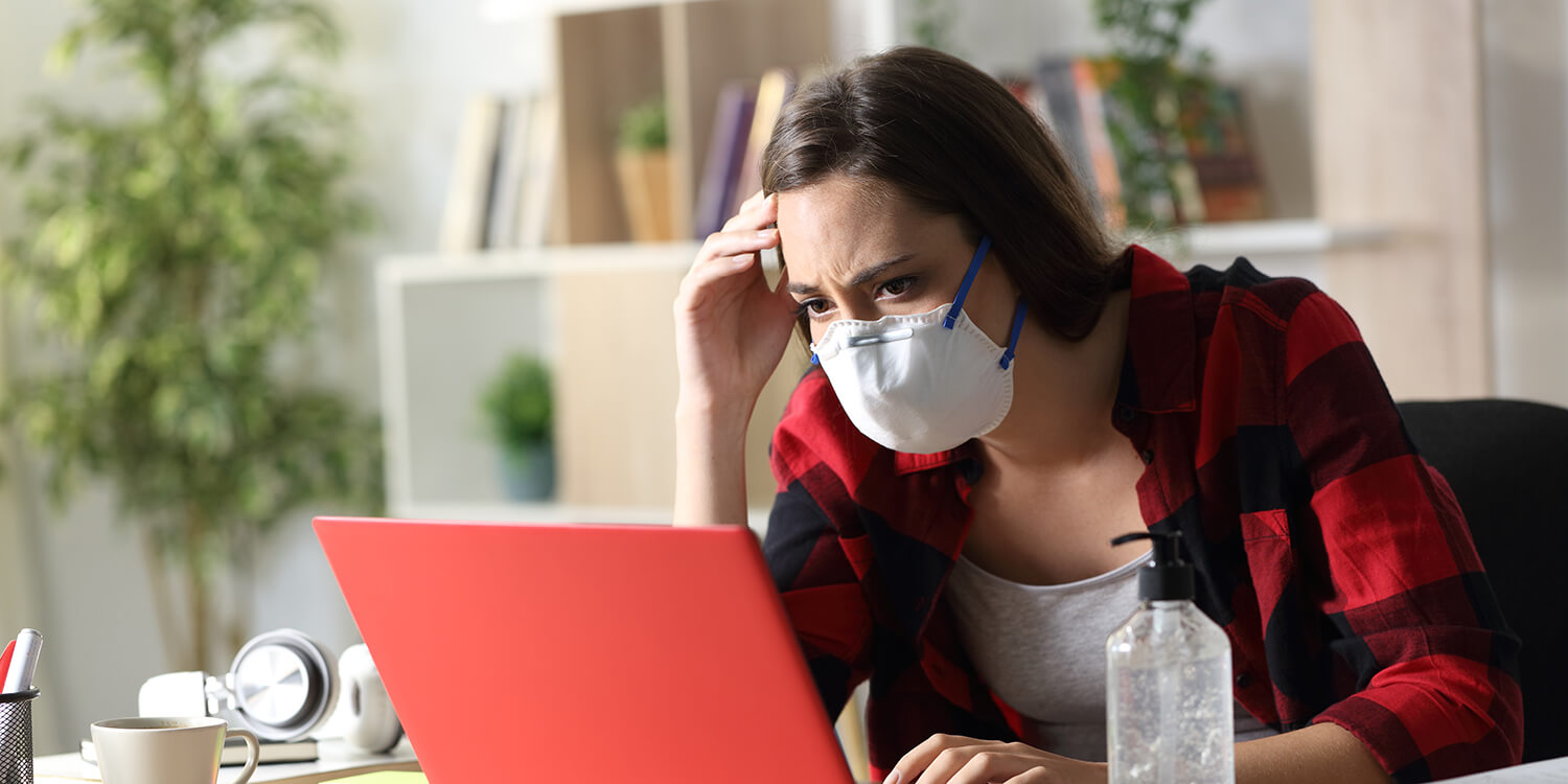 student wearing protective face mask looking at laptop with a concerned expression