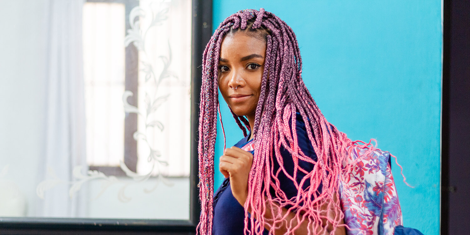 Young black woman with colorful braids and backpack, looking at camera with a serious expression