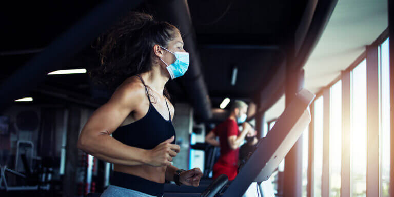Young fit woman running on treadmill in modern fitness gym.
