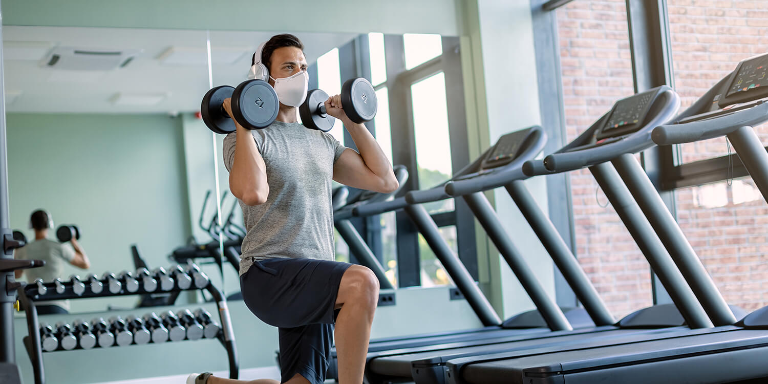 Male athlete wearing face mask while exercising with hand weights in lunge position in a gym