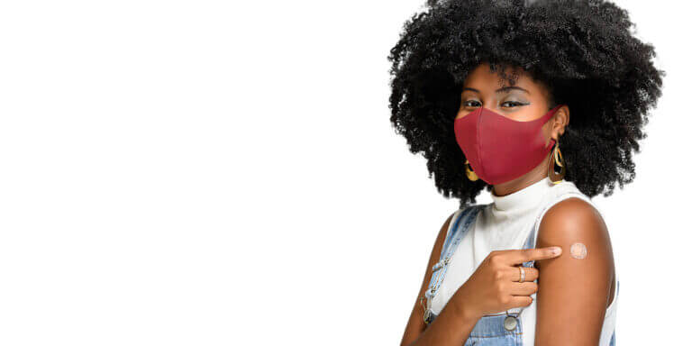 black woman wearing face mask pointing at band aid on arm after receiving covid-19 vaccination