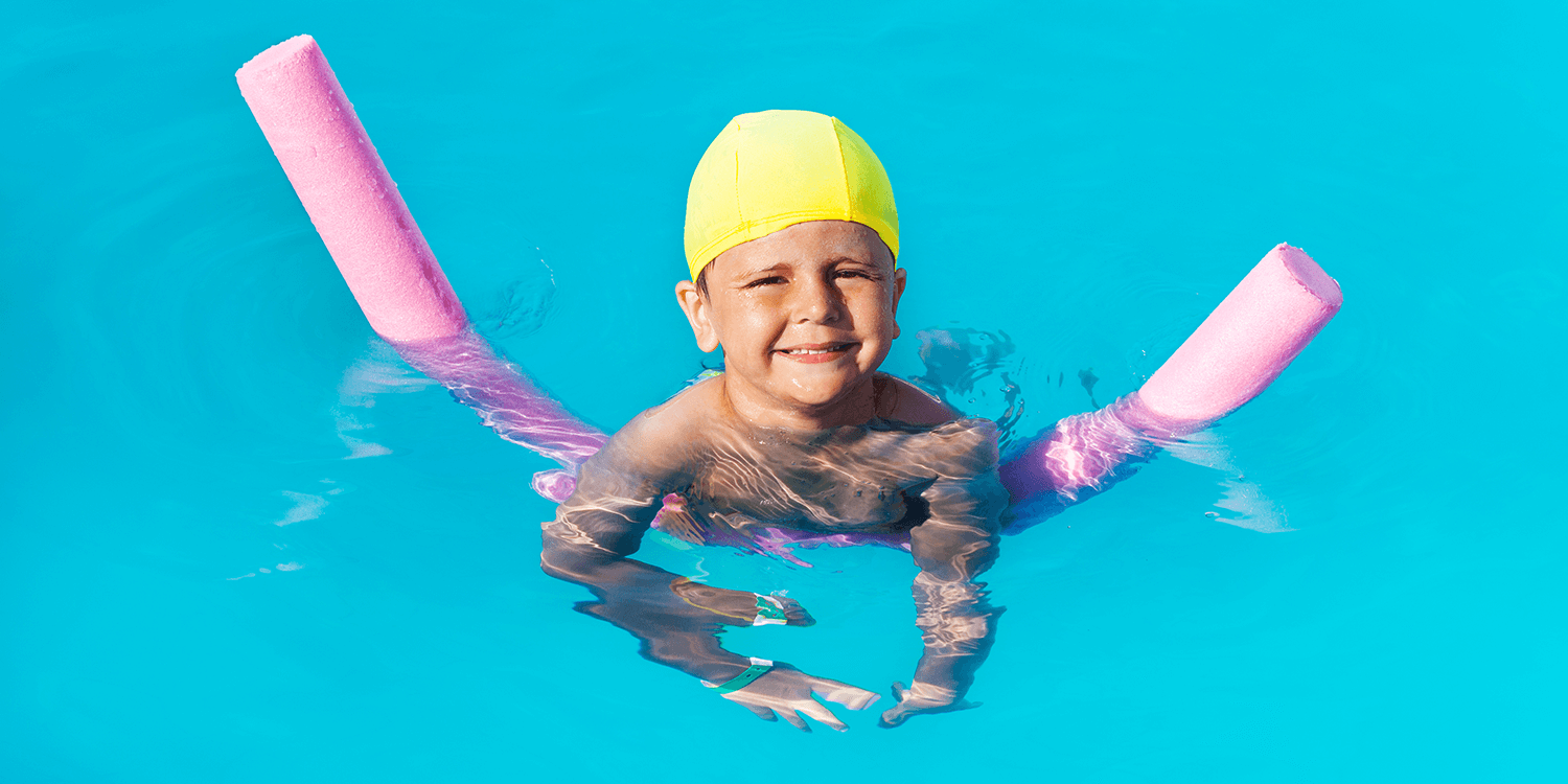 Smiling boy learns how to swim with pool noodle
