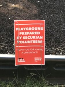 """close up of sign that reads, """"Playground prepared by Securian volunteers. Thank you for making a difference!"""""""
