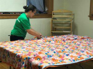 volunteer focused on cutting pieces of fleece for tie blankets