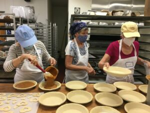 masked bakers assembling sweet potato pies