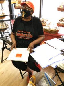Masked Black woman organizing documents