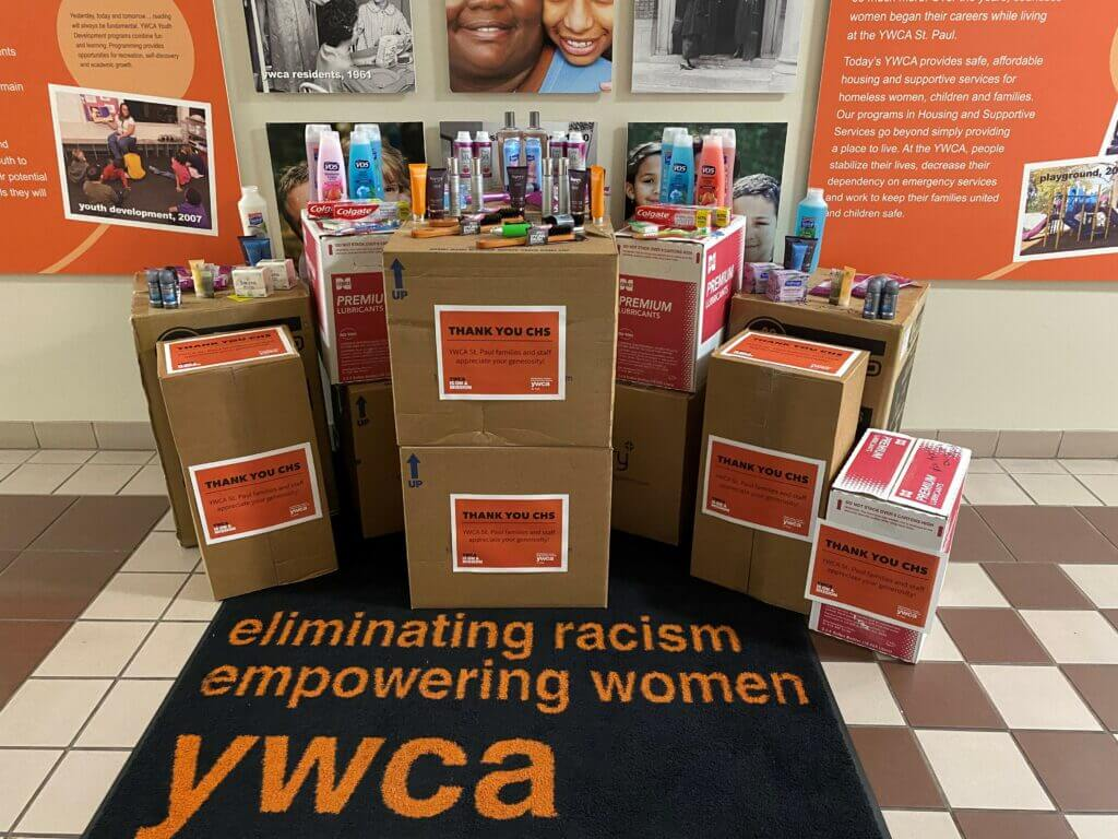 several brown boxes of personal hygiene items, with several displayed on top of the boxes like shampoo, conditioner, deodorant