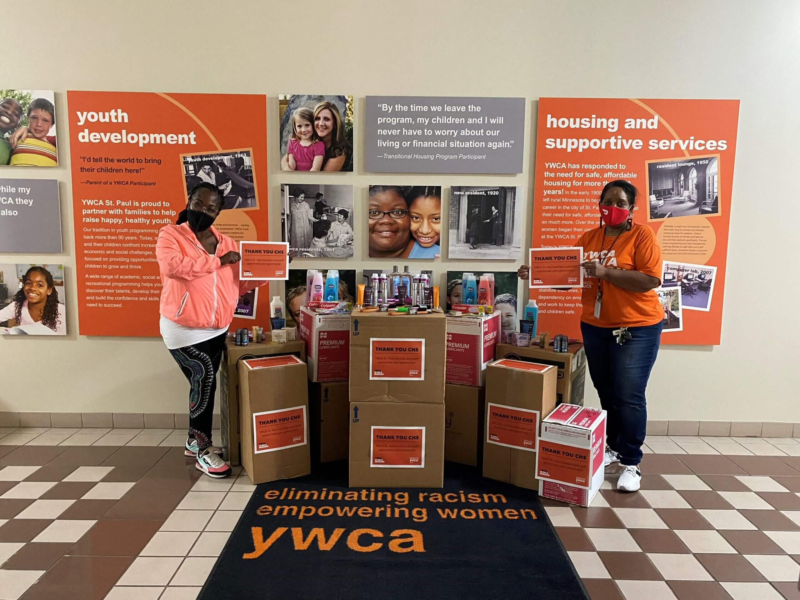 Two YW Staffers (African-American women) stand beside several boxes of personal hygiene items