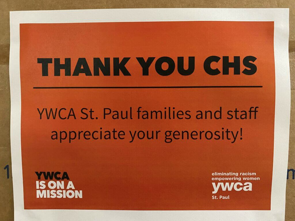 """Close up picture of a paper sign that reads """"Thank you CHS. YWCA St. Paul families and staff appreciate your generosity"""". The text is black on an orange background, with the YWCA St. Paul logo in the bottom corner."""