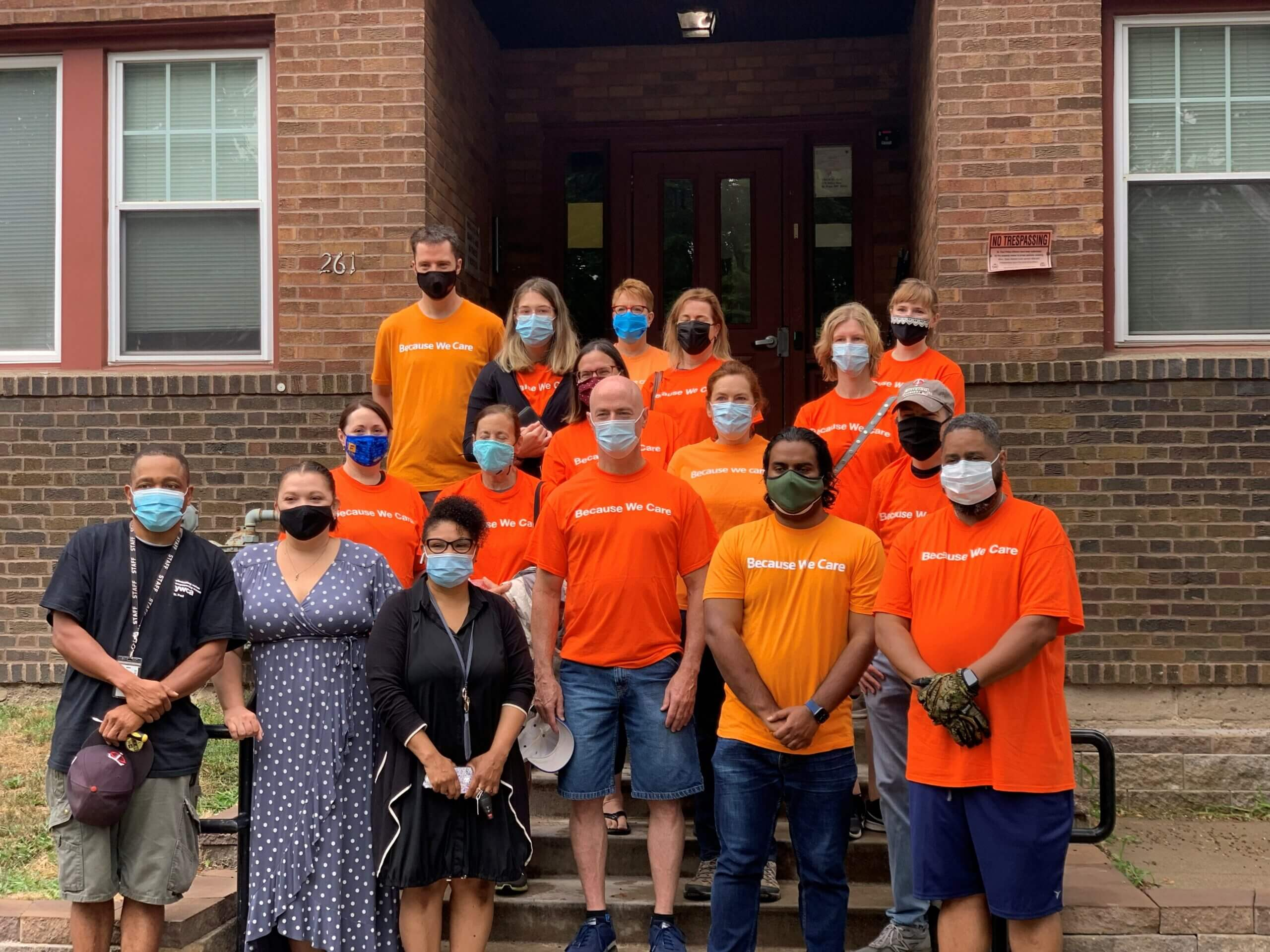 """Group of Thomson Reuters volunteers and YW employees. The group is standing in front of a brick apartment building. Thomson Reuters employees are wearing orange t-shirts that say """"Because We Care"""". Everyone is wearing a mask."""