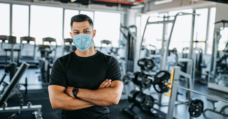 Latino man with hand crossed looking directly at camera. He is wearing a medical-grade face mask. He is standing in a gym and the weight room is visible behind him.