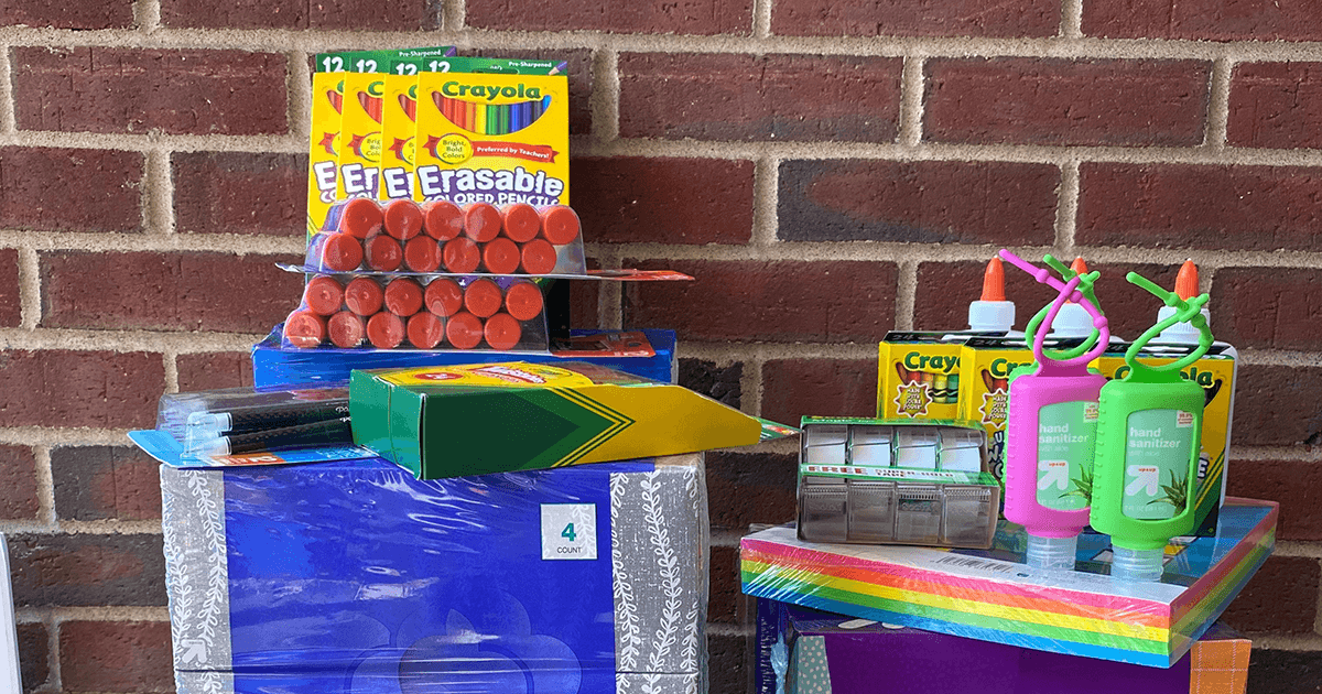 Display of donated school supplies. You can see colored pencils, glue sticks, kleenex boxes, tape, crayons and hand sanitizer