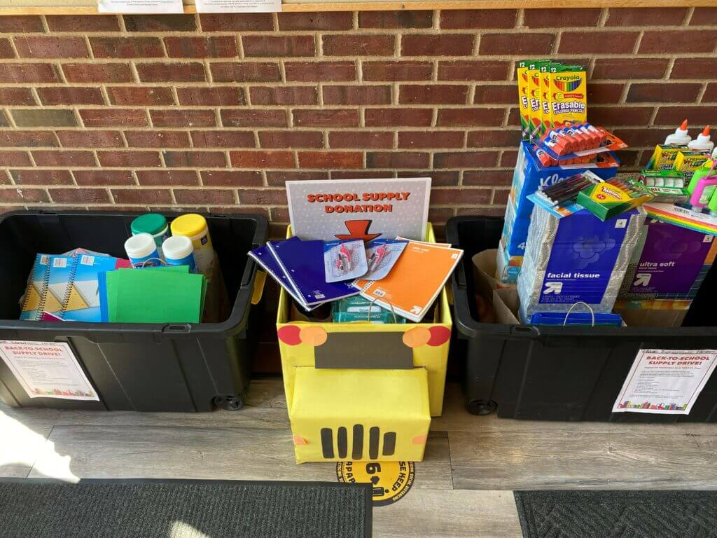 Three large boxes of donated school suplies. You can see clorox wipes, folders, notebooks, scissors, kleenex boxes, and markers. There are additional items in the boxes that aren't quite visible.