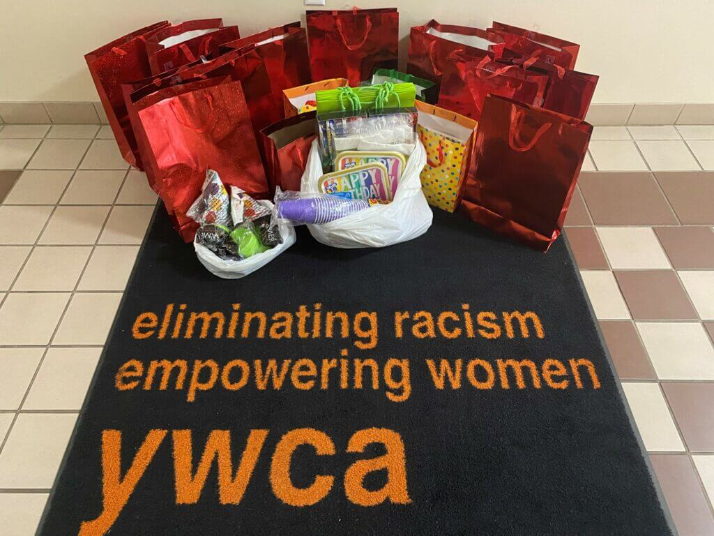 Group of party bag kits displayed on tile floor. YWCA's logo is visible at the bottom of the screen.