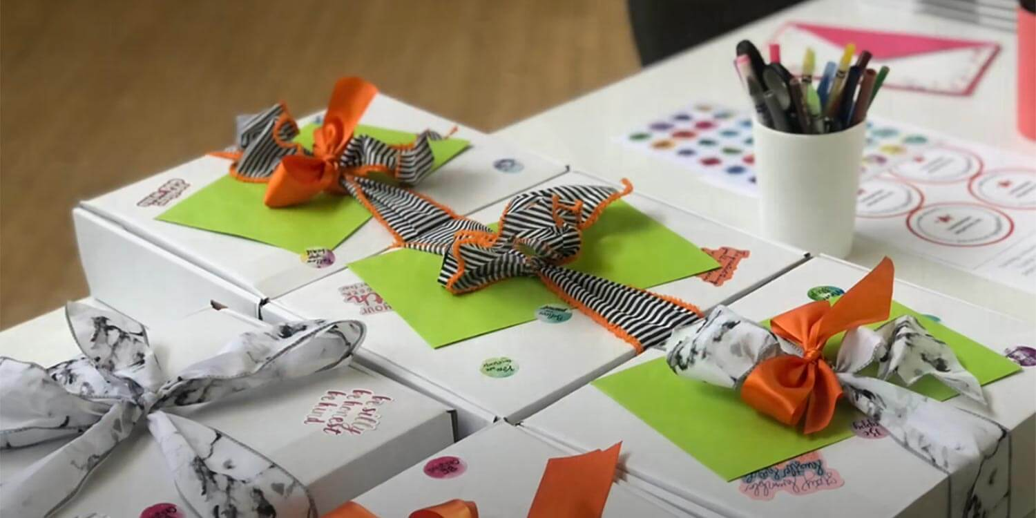 close up of several self-care kits on a table. The kits are white boxes that have been wrapped with colorful bows and decorated with stickers.